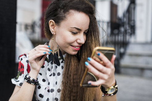 UK, London, young woman watching her earring with the aid of her smartphone - MAUF000670