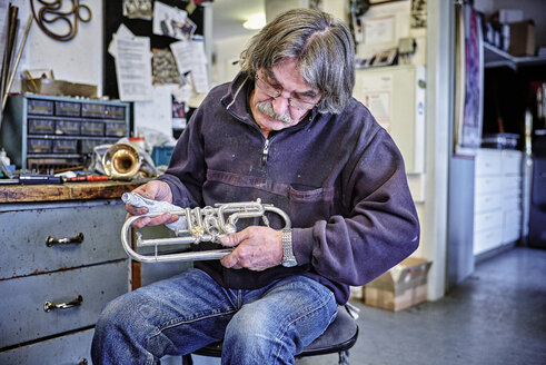 Instrument maker cleaning trumpet in workshop - DIKF000204