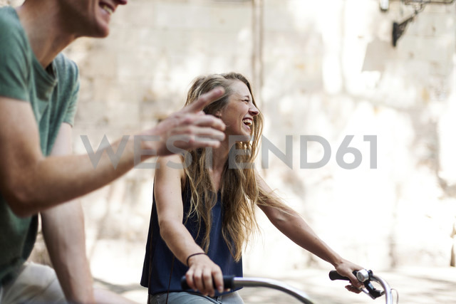 Laughing woman with bicycles beside her partner - VABF000593