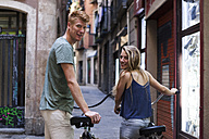 Spain, Barcelona, couple with bicycles in front of an alley - VABF000599
