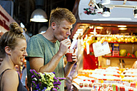 Man drinking smoothie on a street market - VABF000605
