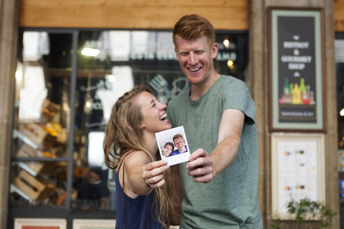 Happy couple showing selfie of their wedding in front of a coffee shop - VABF000614