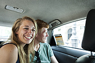 Portrait of grinning woman sitting in taxi with her boyfriend in the background - VABF000623