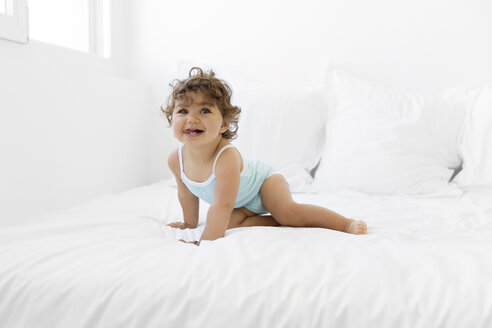Portrait of baby girl crouching on a white bed with her tongue sticking out - LITF000376