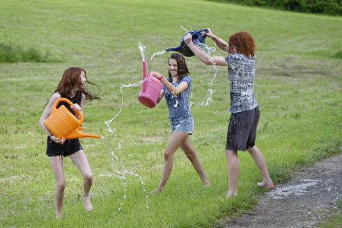 Three teenagers with watering cans splashing with water - LBF001442