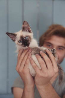 Young man holding kitten, close-up - RTBF000237