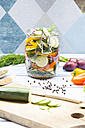 Glass of pickled courgette and bell pepper, preparation with different spices - LVF004992