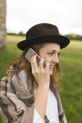 Young woman wearing hat telephoning with smartphone at countryside - BOYF000419