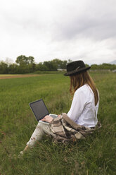 Woman sitting on a meadow using laptop - BOYF000425