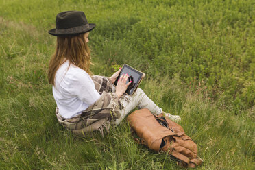 Woman sitting on a meadow using digital tablet - BOYF000428