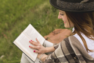 Young woman sitting on a meadow reading a book - BOYF000437