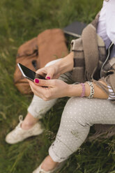 Young woman on a meadow listening music with earphones and smartphone - BOYF000440