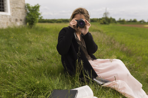 Woman sitting on a meadow taking picture of viewer - BOYF000446