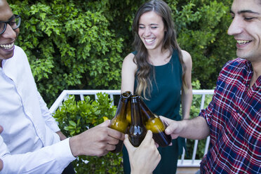 Friends toasting with bottles of beer in a garden - ABZF000721