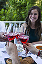 Friends toasting with lambrusco wine during a summer dinner - ABZF000727