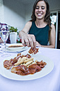 Woman taking a piece of spanish ham - ABZF000730