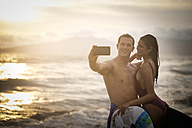 Young couple taking a selfie on beach at twilight - ABAF002058