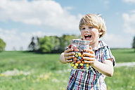 Happy boy outdoors holding glass with jelly beans - MJF001916