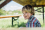 Boy under beer table in meadow - MJF001919