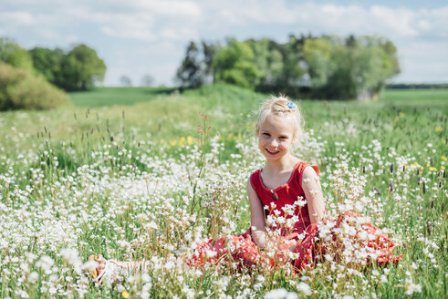 Smiling girl sitting in meadow - MJF001922