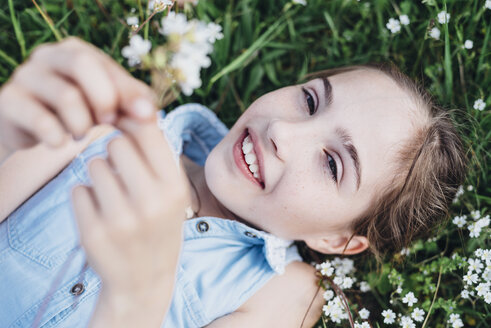 Smiling girl lying in flower meadow - MJF001925