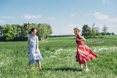 Two girls with hula hoop in meadow - MJF001934