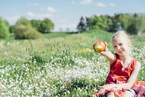 Smiling girl sitting in meadow holding an apple - MJF001940