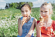 Two girls in meadow eating ice cream cones - MJF001946