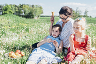 Mother and two girls relaxing in meadow - MJF001955