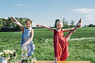 Two girls doing gymnastics in meadow - MJF001958