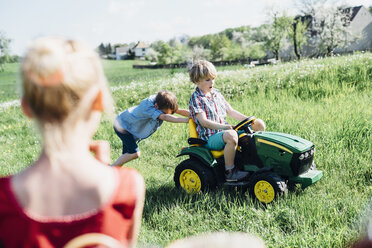 Children playing with toy tractor on meadow - MJF001961