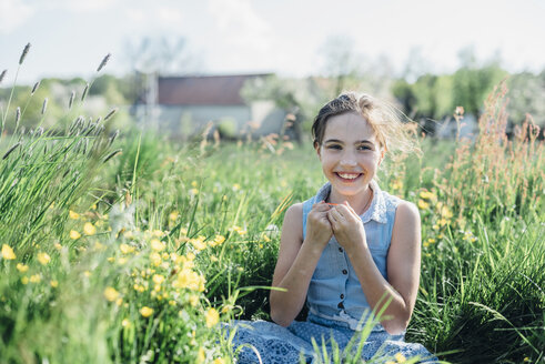 Smiling girl sitting in flower meadow - MJF001970
