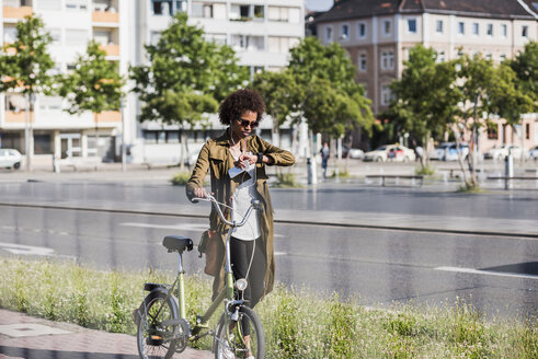 Young woman with with bicycle checking the time - UUF007733