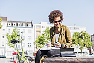 Smiling young woman sitting on a bench using smartphone and digital tablet - UUF007736