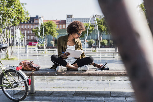 Young woman sitting on a bench with notebbok looking at digital tablet - UUF007739