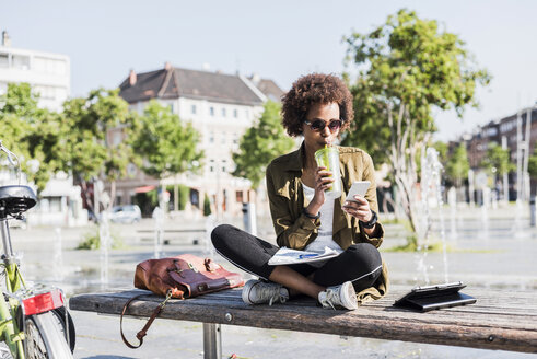 Young woman sitting on a bench drinking beverage while looking at her smartphone - UUF007742