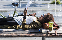 Smiling woman lying on a bench reading notes - UUF007745