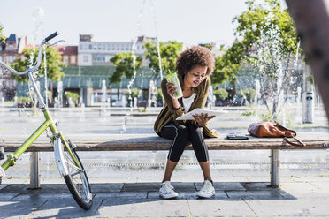 Young woman sitting on a bench with beverage reading notes - UUF007748