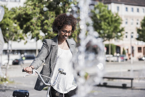 Portrait of smiling woman with bicycle listening music with earphones - UUF007751