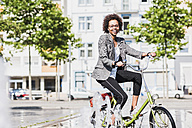 Portrait of smiling woman on bicycle - UUF007754