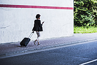 Businesswoman with baggage and smartphone walking down the street - UUF007757