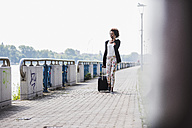 Smiling businesswoman with  baggage telephoning with smartphone at riverside - UUF007760