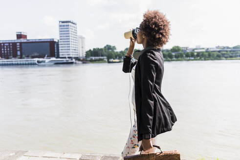 Germany, Mannheim, young businesswoman drinking coffee to go while walking at riverside - UUF007769