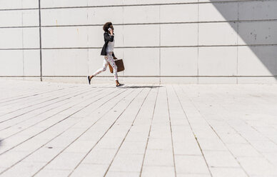 Businesswoman with briefcase running while telephoning with smartphone - UUF007772