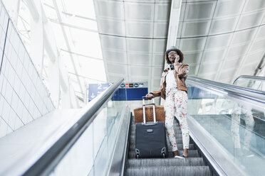 Young woman with baggage standing on escalator telephoning with smartphone - UUF007775