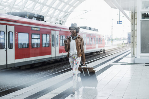 Young woman with trolley bag and smartphone at platform - UUF007778