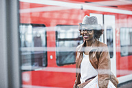 Smiling young woman waiting at platform in front of a train - UUF007781