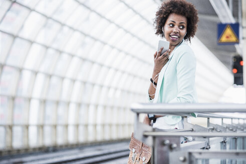 Young woman with earphones telephoning with smartphone while waiting at platform - UUF007784