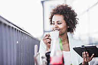 Smiling young woman with cup of coffee and digital tablet in a street cafe - UUF007796