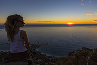 South Africa, Cape Town, teenage girl enjoying the sunset on top of mountain lion's head - YRF000113